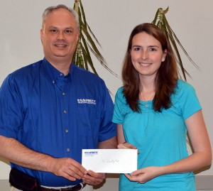 Derek Barr, Hardy Telecommunications director of customer service and sales, marketing and human resources, presents a $400 donation for the Tri-County Fair Barn project to Fair Goat Committee member Jessica Wilkins.