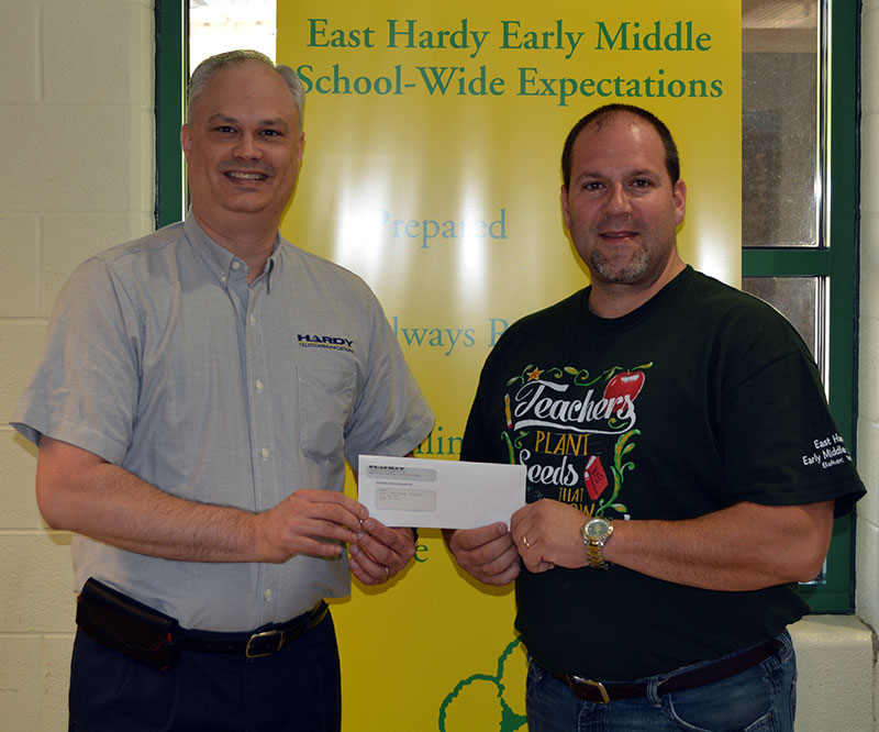 (Left to right): Derek Barr, director of customer service and sales, marketing and human resources for Hardy Telecommunications, presents a $500 donation to East Hardy Early Middle School Principal Don Rhodes to support the school's project to bring updated technology to the school's students and teachers.